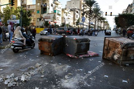 Supporters of caretaker Lebanese Prime Minister Saad Hariri block a main road by garbage containers in Beirut, Lebanon