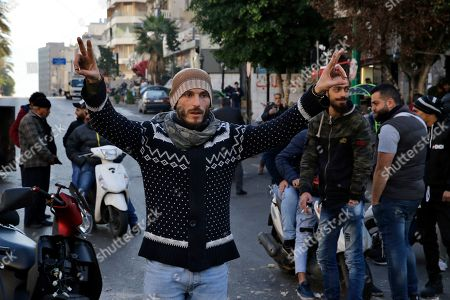 A supporter of caretaker Lebanese Prime Minister Saad Hariri shows a victory sign as others block a main road in Beirut, Lebanon