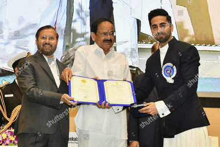 Vice President Venkaiah Naidu, center, presents the national film award to Bollywood actor Ayushmann Khurrana, right, who shared the best actor award with actor Vicky Kaushal during the national film awards ceremony in New Delhi, India, Monday, Dec.23, 2019. Information and Broadcasting Minister Prakash Javdekar is on left