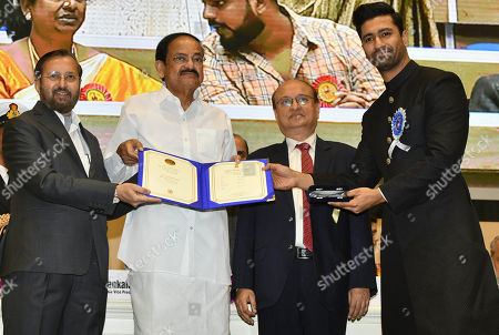 Vice President Venkaiah Naidu, second left, presents the national film award to Bollywood actor Vicky Kaushal, right, who shared the best actor award with actor Ayushmann Khurrana during the national film awards ceremony in New Delhi, India, Monday, Dec.23, 2019. Information and Broadcasting Minister Prakash Javdekar is on left