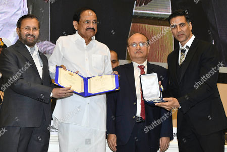 Vice President Venkaiah Naidu, second left, presents the award for best film on social issues to Padman, being received by Bollywood actor Akshay Kumar, right, during the national film awards ceremony in New Delhi, India, Monday, Dec.23, 2019. Information and Broadcasting Minister Prakash Javdekar is on left
