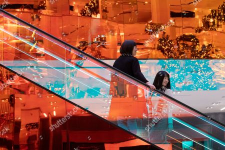 Shows customers riding the escalators designed by Dutch architect Rem Koolhaas at the Saks Fifth Avenue Flagship in New York. Luxury department stores like Neiman Marcus and Saks Fifth Avenue once ruled among the affluent set. Now, they're fighting a tough battle to lure younger shoppers faced with a lot more shopping choices, including second-hand retailers and fashion rental companies