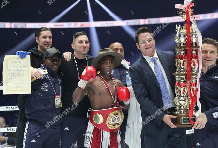 South African champion Moruti Mhtalane, wearing his belt, poses for photographers after beating Japanese challenger Akira Yaegashi in their IBF flyweight world boxing title match in Yokohama, southwest of Tokyo,. Mhtalane defended his title by a technical knockout in the ninth round