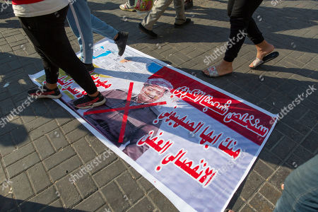"""Protesters walk on a poster with a defaced picture of the Chairman of the Kurdish Democratic Party and former president of the Iraqi Kurdistan Region Masoud Barzani, with Arabic that reads, """"we will relieve our Kurdish people from you, a rotten separatist Zionist,"""" during the ongoing protests in Tahrir square, Baghdad, Iraq"""