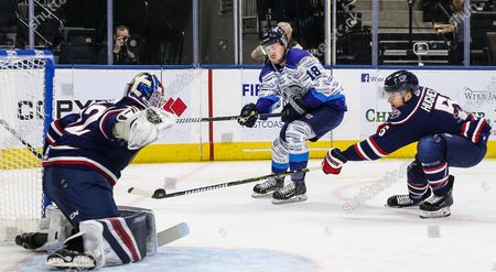 Jacksonville Icemen right wing Regan Nagy (18) has his shot blocked by South Carolina Stingrays defenseman Tommy Hughes (5) in front of goaltender Logan Thompson (32) during the first period of an ECHL hockey game at Veterans Memorial Arena in Jacksonville, Fla., [Gary Lloyd McCullough/CSM]