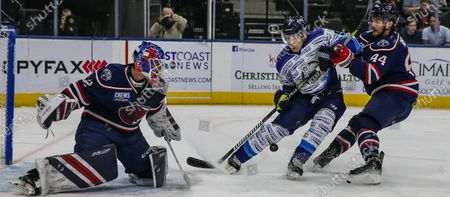 Jacksonville Icemen forward Alexis D'Aoust (9) and South Carolina Stingrays defenseman Jaynen Rissling (44) vie for the puck in front of goaltender Logan Thompson (32) during the first period of an ECHL hockey game at Veterans Memorial Arena in Jacksonville, Fla., [Gary Lloyd McCullough/CSM]