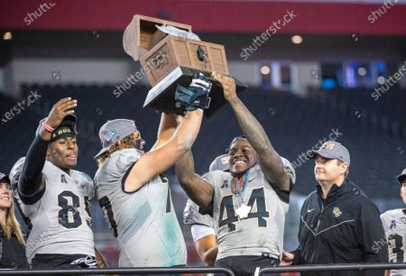 Stock Photo of Tampa, FL, U.S: (Right) UCF head coach Josh Heupel watches as the Gasparilla trophy is hoisted by L-R UCF tight end Anthony Roberson (89), UCF offensive lineman Jake Brown (77) and UCF linebacker Nate Evans (44) during awards ceremony of the Bad Boy Mowers Gasparilla Bowl between UCF Knights and the Marshall Thundering Herd. Central Florida defeated -25 at Raymond James Stadium in Tampa, FL