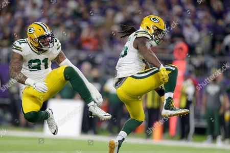 Green Bay Packers outside linebacker Za'Darius Smith, right, celebrates with teammate Preston Smith after sacking Minnesota Vikings quarterback Kirk Cousins during the second half of an NFL football game, in Minneapolis
