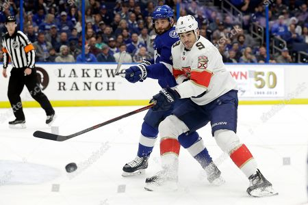 Pat Maroon, Brian Boyle. Florida Panthers center Brian Boyle (9) tries to deflect a shot as he battles for position with Tampa Bay Lightning left wing Pat Maroon (14) during the first period of an NHL hockey game, in Tampa, Fla
