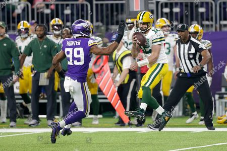 Green Bay Packers quarterback Aaron Rodgers (12) is sacked by Minnesota Vikings defensive end Danielle Hunter (99) during the first half of an NFL football game, in Minneapolis