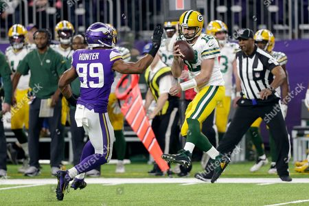 Green Bay Packers quarterback Aaron Rodgers (12) is about to be sacked by Minnesota Vikings defensive end Danielle Hunter (99) during the first half of an NFL football game, in Minneapolis
