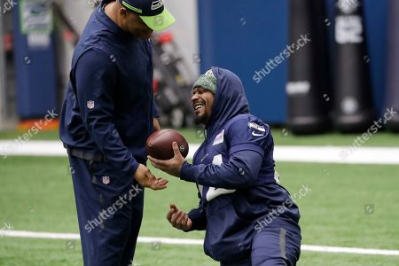 Seattle Seahawks running back Marshawn Lynch, right, talks with defensive coordinator Ken Norton Jr. during warm-ups at the team's practice facility, in Renton, Wash. When Lynch played his last game for the Seattle Seahawks in 2016, the idea of him ever wearing a Seahawks uniform again seemed preposterous. Yet, here are the Seahawks getting ready to have Lynch potentially play a major role on Sunday against San Francisco with the NFC West title on the line