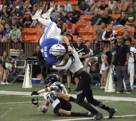 Brigham Young Cougars quarterback Zach Wilson (1) get hit into a helicopter spin by Hawaii Rainbow Warriors defensive back Nalu Emerson (28) and Hawaii Rainbow Warriors defensive back Eugene Ford (8) forcing a fumble recovered by Hawaii Rainbow Warriors defensive lineman Manly Williams (49) during a game at the SoFi Hawaii Bowl between the Brigham Young Cougars and the Hawaii Rainbow Warriors at the Stan Sheriff Center in Honolulu, HI - Michael Sullivan/CSM
