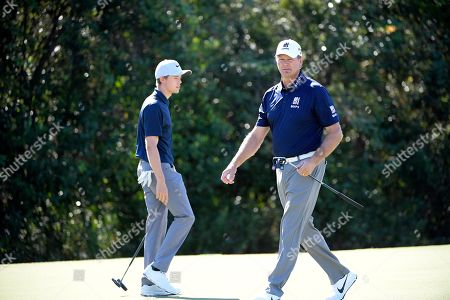 Retief Goosen, right, and his son, Leo Goosen, walk on the seventh green during the first round of the Father Son Challenge golf tournament, in Orlando, Fla