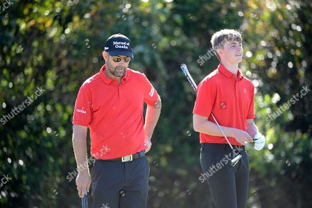 Padraig Harrington, left, and his son, Paddy Harrington, wait to putt on the seventh green during the first round of the Father Son Challenge golf tournament, in Orlando, Fla