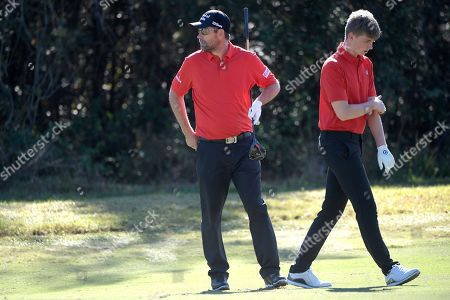 Stock Photo of Padraig Harrington, left, and his son, Paddy Harrington, walk on the seventh green during the first round of the Father Son Challenge golf tournament, in Orlando, Fla