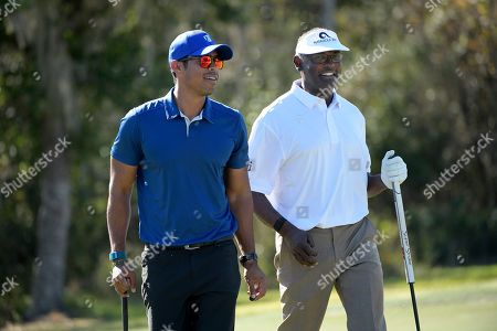 Stock Image of Qass Singh, left, and his father, Vijay Singh, walk off the seventh green after making their putts during the first round of the Father Son Challenge golf tournament, in Orlando, Fla