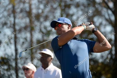 Stock Photo of Qass Singh, right, son of Vijay Singh, watches his tee shot on the eighth hole during the first round of the Father Son Challenge golf tournament, in Orlando, Fla