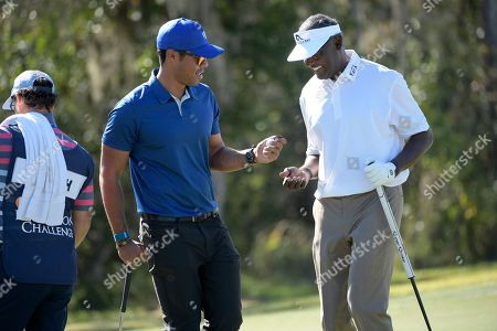 Qass Singh, left, and his father, Vijay Singh, share a laugh after making their putts on the seventh green during the first round of the Father Son Challenge golf tournament, in Orlando, Fla