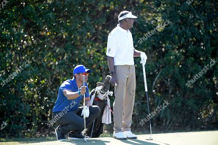 Qass Singh, left, and his father, Vijay Singh, wait to putt on the seventh green during the first round of the Father Son Challenge golf tournament, in Orlando, Fla
