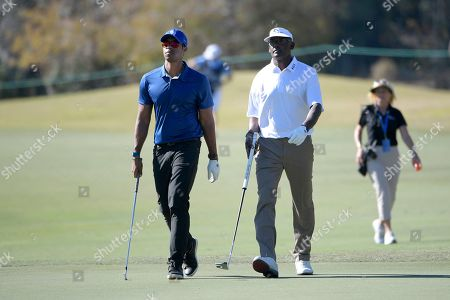 Qass Singh, left, and his father, Vijay Singh, walk to the seventh green after hitting from the fairway during the first round of the Father Son Challenge golf tournament, in Orlando, Fla
