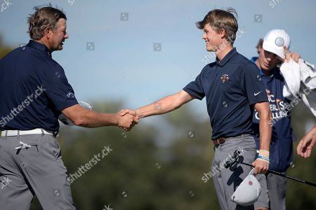 Retief Goosen, left, shakes hands with his son Leo Goosen after making their putts on the 18th green during the first round of the Father Son Challenge golf tournament, in Orlando, Fla