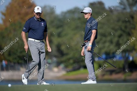 Retief Goosen, left, and his son Leo Goosen line up their putts on the 18th green during the first round of the Father Son Challenge golf tournament, in Orlando, Fla