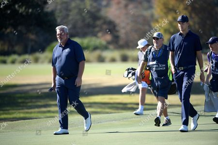 Stock Photo of Darren Clarke, left, walks with his son, Tyrone Clarke, second from right, on the seventh fairway during the first round of the Father Son Challenge golf tournament, in Orlando, Fla