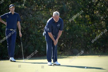 Tyrone Clarke, left, watches his father Darren Clarke line up a putt on the seventh green during the first round of the Father Son Challenge golf tournament, in Orlando, Fla