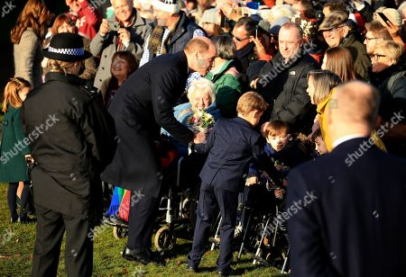 Britain's Prince William, Duke of Cambridge and his son Prince George greet the public after attending a Christmas day service at the St Mary Magdalene Church in Sandringham in Norfolk, England