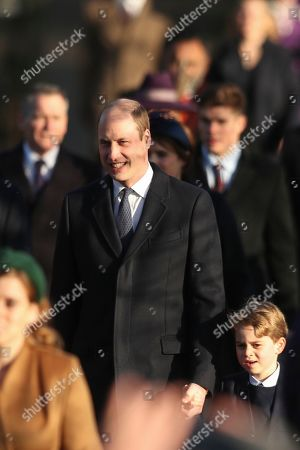 Britain's Prince William, Duke of Cambridge, center, holds the hand of his son Prince George as he arrives to attend the Christmas day service at St Mary Magdalene Church in Sandringham in Norfolk, England
