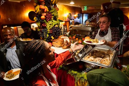 Tim Allen, Tiffany Haddish. Comedian Tim Allen passes a plate to fellow comedian Tiffany Haddish as they serve the community Christmas dinner at the Laugh Factory for the 40th Annual Free Christmas Dinner at the Laugh Factory in the Hollywood section of Los Angeles, . Top comedians served guests and performed live shows following each meal served throughout the day. Other celebrities helped, as well. The Factory welcomed anyone who has fallen on difficult times or whose children could use a toy and a warm holiday meal