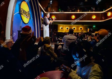 Six-year-old Ja-Niyha, foreground, looks at her phone while comedian Tim Allen performs onstage at the annual free Christmas dinner at the Laugh Factory in the Hollywood section of Los Angeles, . Top comedians served guests and performed live shows following each meal served throughout the day. Other celebrities helped, as well. The Factory welcomed anyone who has fallen on difficult times or whose children could use a toy and a warm holiday meal