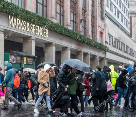 Stock Photo of Wind and rain hamper shoppers in Oxford Street as the Boxing Day bargain hunters brave the cold and wet weather in the West End for a chance to get discounted designer items.