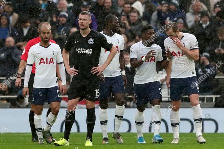 Brighton's Adam Webster, foreground, reacts after Tottenham's Harry Kane, right, scored the opening goal during the English Premier League soccer match between Tottenham Hotspur and Brighton & Hove Albion at the Tottenham Hotspur Stadium in London, England