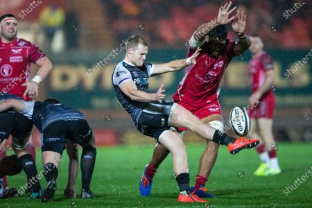 Aled Davies of Ospreys kicks as he comes under pressure from Sam Lousi of Scarlets
