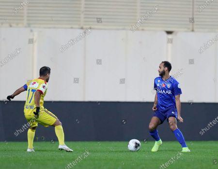 Stock Photo of AL- Hazm's Fares Al-Eaiafi (L) in action against Al-Hilal's Abdullah Otayf (R), during the Saudi Professional League soccer match between AL- Hazm and Al-Hilal at Al Hazm Club Stadium in Ar Rass, Saudi Arabia, 26 December 2019.