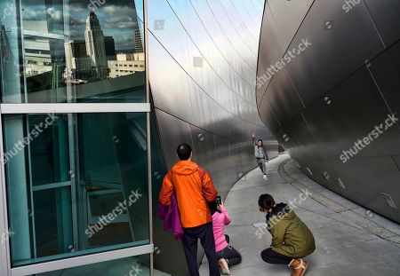 Stock Photo of Heavy storm clouds are reflected in a window over Los Angeles City Hall, left, while Chinese tourists take photos along a walkway at the Walt Disney Concert Hall on . A cold and blustery winter storm unleashed a deluge of rain and snow on Southern California, triggering tornado warnings and snarling post-Christmas travel on major routes