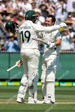 Australia's James Pattinson, left, congratulates teammate Travis Head on scoring a century against New Zealand during play in their cricket test match in Melbourne, Australia