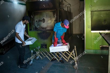 "Cemetery workers prepare the corpse of 11-month-old Anabella for her cremation at a cemetery in Maracaibo, Venezuela. Anabella's father Fernando Gonzalez said doctors told him his daughter died of malnutrition, however, ""Sepsis. Central nervous system infection"" was written on her death certificate. Gonzalez said he was thankful his boss at the cemetery donated his daughter's wake and cremation services, because he didn't have the money for a funeral"
