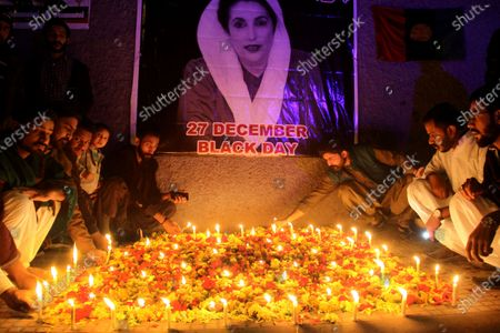 Supporters of slain former Pakistani Prime Minister Benazir Bhutto light candles in front of a poster depicting Bhutto on the twelth anniversary of Bhutto's assassination in Hyderabad, Pakistan, 27 December 2019. Benazir Bhutto was killed in an attack during an election campaign in Rawalpindi in December 2007.