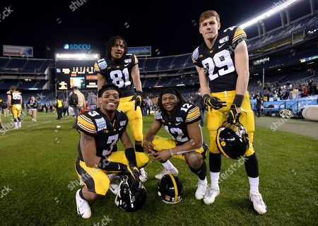 Iowa wide receivers Tyrone Tracy Jr. (3), Desmond Hutson (81), Brandon Smith (12) and Jackson Ritter (29) pose for a photograph following the Holiday Bowl NCAA college football game against Southern California, in San Diego. Iowa won 49-24