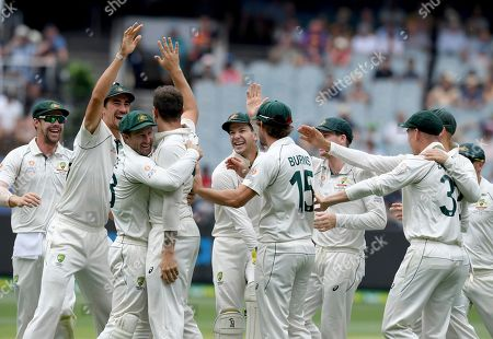 Australia players celebrate with James Pattinson after capturing the wicket of New Zealand's BJ Watling during a cricket test match in Melbourne, Australia