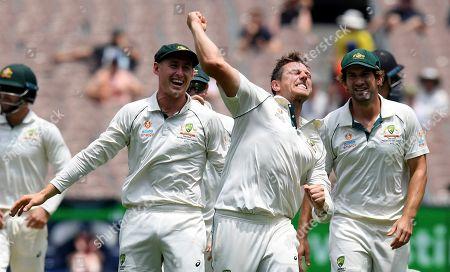 Australia's Marnus Labuschagne, left, James Pattinson, center, and Australia's Joe Burns, right, celebrate the the wicket of New Zealand's Mitchell Santner during a cricket test match in Melbourne, Australia