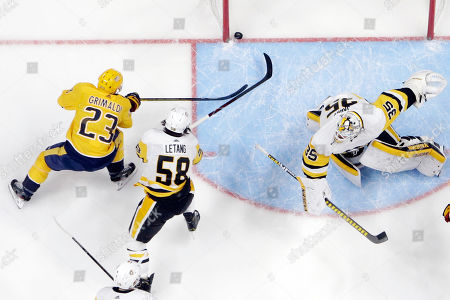 Rocco Grimaldi, Kris Letang, Tristan Jarry. Pittsburgh Penguins defenseman Kris Letang (58) and Nashville Predators right wing Rocco Grimaldi (23) reach for the puck behind Penguins goaltender Tristan Jarry (35) during the first period of an NHL hockey game, in Nashville, Tenn. The goal was credited to Predators right wing Craig Smith