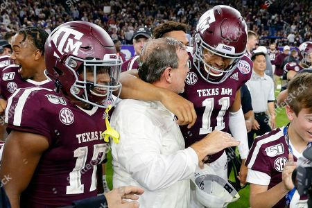 Texas A&M wide receiver Ainias Smith (17), coach Jimbo Fisher and quarterback Kellen Mond (11) celebrate after the team's 24-21 win against Oklahoma State in the Texas Bowl NCAA college football game, in Houston