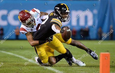 Iowa wide receiver Brandon Smith, right, reaches forward as he goes out of bounds as he is tackled by Southern California cornerback Olaijah Griffin during the first half of the Holiday Bowl NCAA college football game, in San Diego
