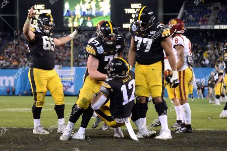 Iowa wide receiver Brandon Smith (12) is helped up by offensive lineman Mark Kallenberger (71) after scoring a touchdown during the second half against Southern California in the Holiday Bowl NCAA college football game, in San Diego. Iowa won 49-24