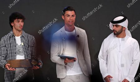 (L-R) Portuguese interantionals Joao Felix of Atletico Madrid, Cristiano Ronaldo of Juventus Turin, and Dubai Crown Prince Sheikh Mansour bin Mohammed bin Rashid Al Maktoum pose during the 14th edition of Dubai International Sports Conference in Dubai, United Arab Emirates, 28 December 2019. The conference was launched in 2006 to bring football stakeholders together.