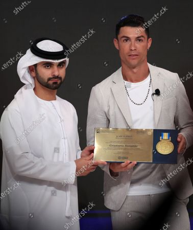 Stock Photo of Portuguese international Cristiano Ronaldo of Juventus Turin (R) receives a Honor Certificate of Appreciation from HH Sheikh Mansour bin Mohammed bin Rashid Al Maktoum(L), President of the Dubai International Marine Club during the 14th edition of Dubai International Sports Conference in Dubai, United Arab Emirates, 28 December 2019. The conference was launched in 2006 to bring football stakeholders together.